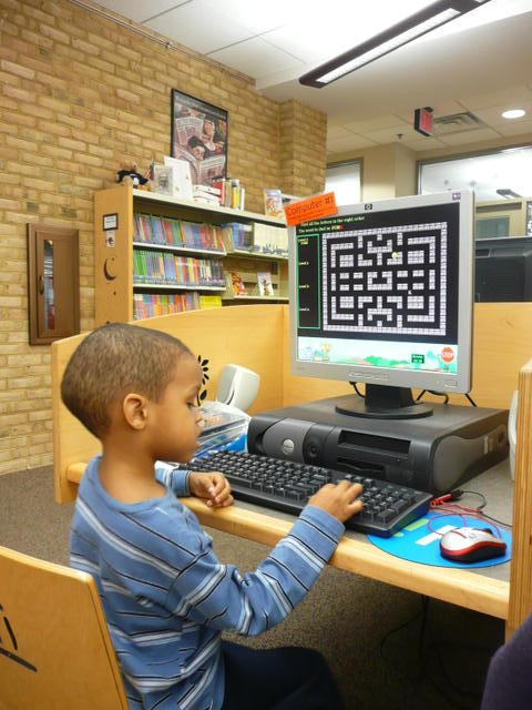 picture of child using computer in library